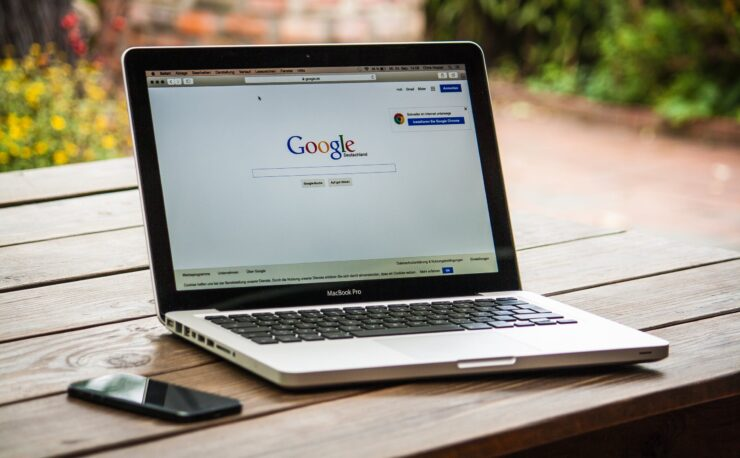 A macbook pro on a table with Google search bar on the screen