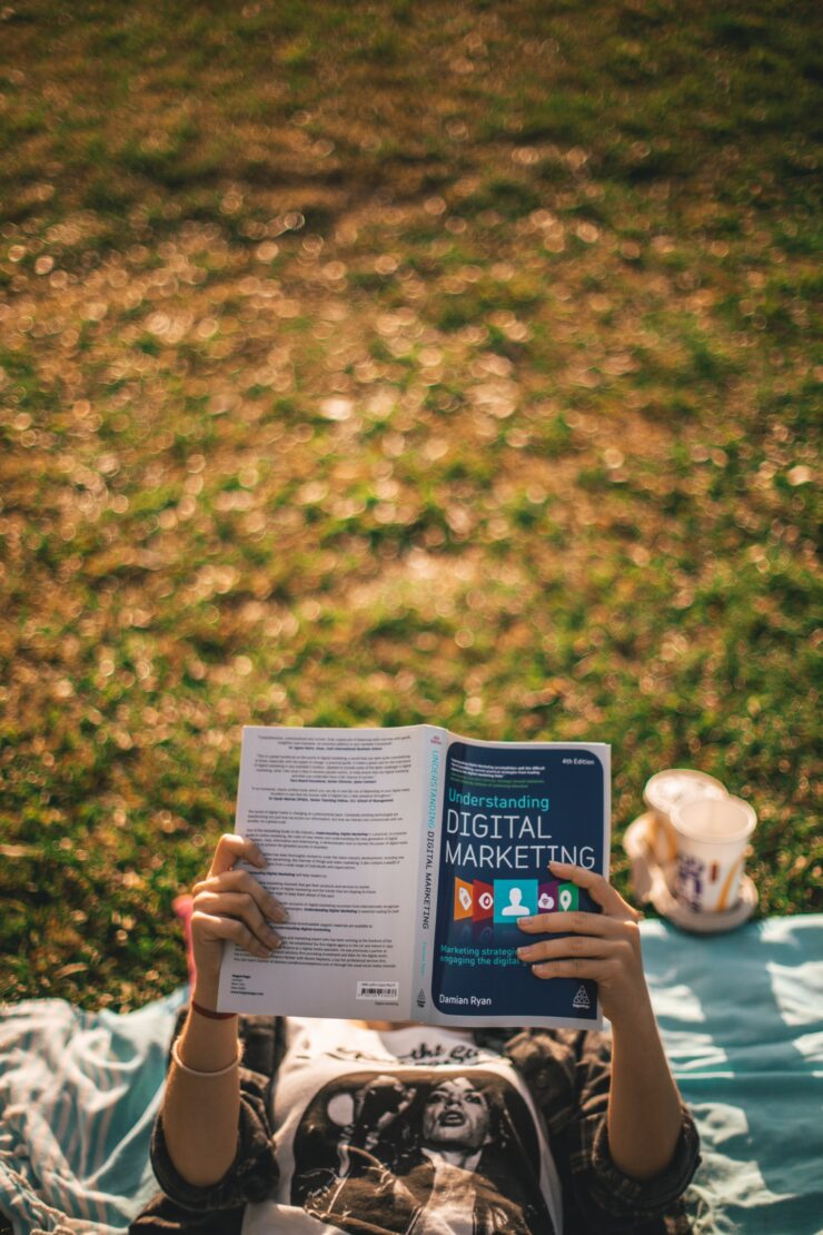 Somebody lays down on the grass to read the book about digital marketing to understand marketing techniques as a crowd marketing