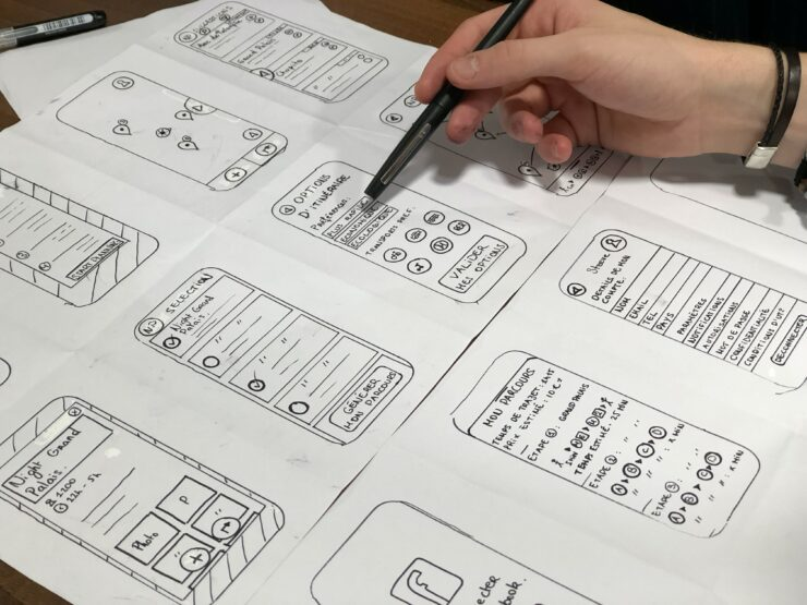UX designrer is drawing mobile layouts on a paper