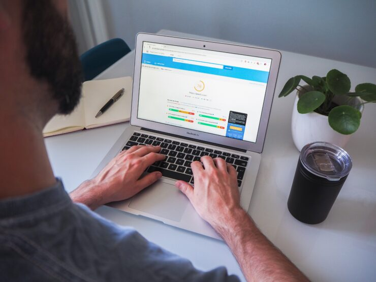 A man is using Google PageSpeed Insights on a laptop to measure a site speed