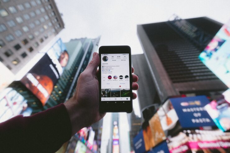 There is an example how people can use social media. Man stands in the centre of city and use social media to find a some business