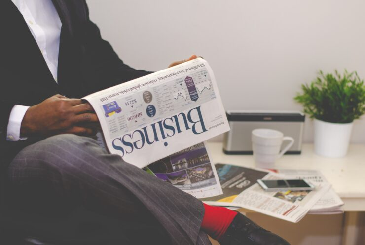 A man in the suit sits and reads a business newspaper