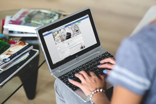 Woman seets and check her social media on a laptop