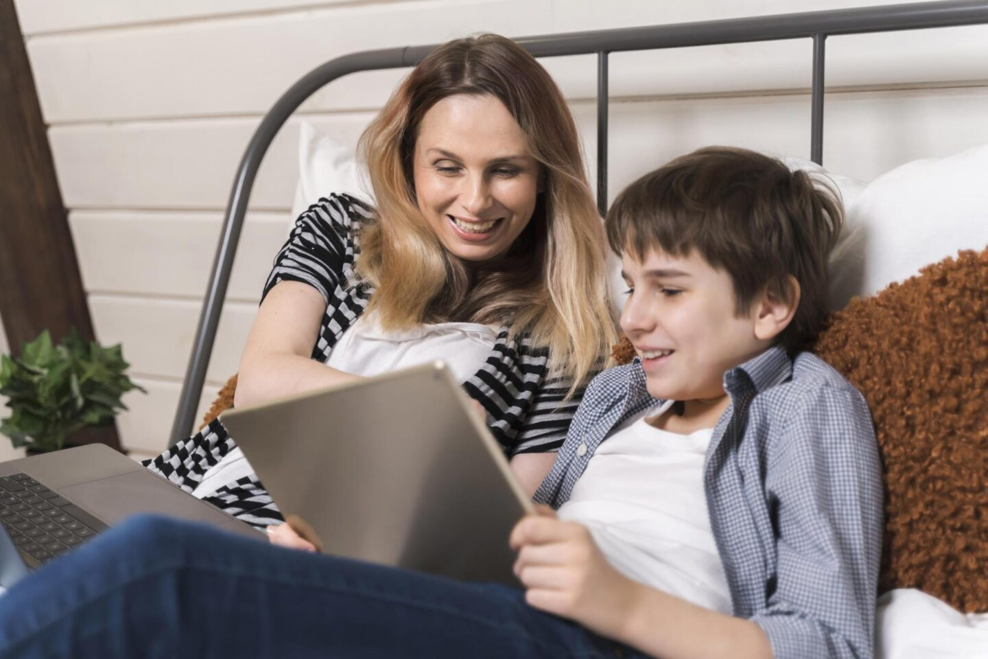 Happy mom and her son are playing math games on tablet PC