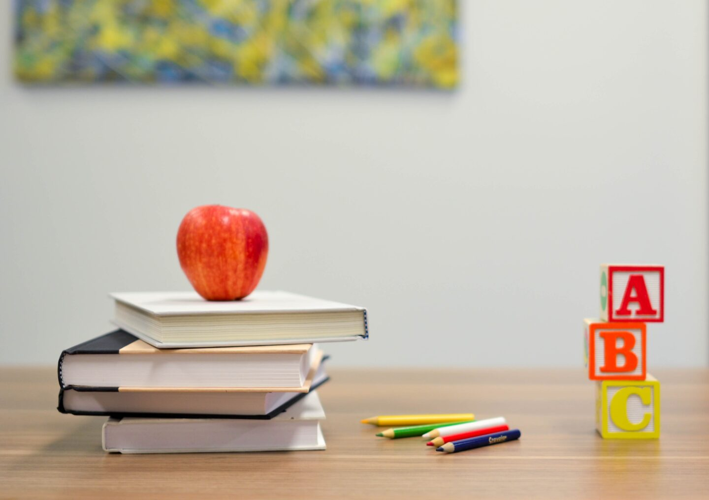 A stack of books with a red apple on top is on desk that symbolizes learning and teaching