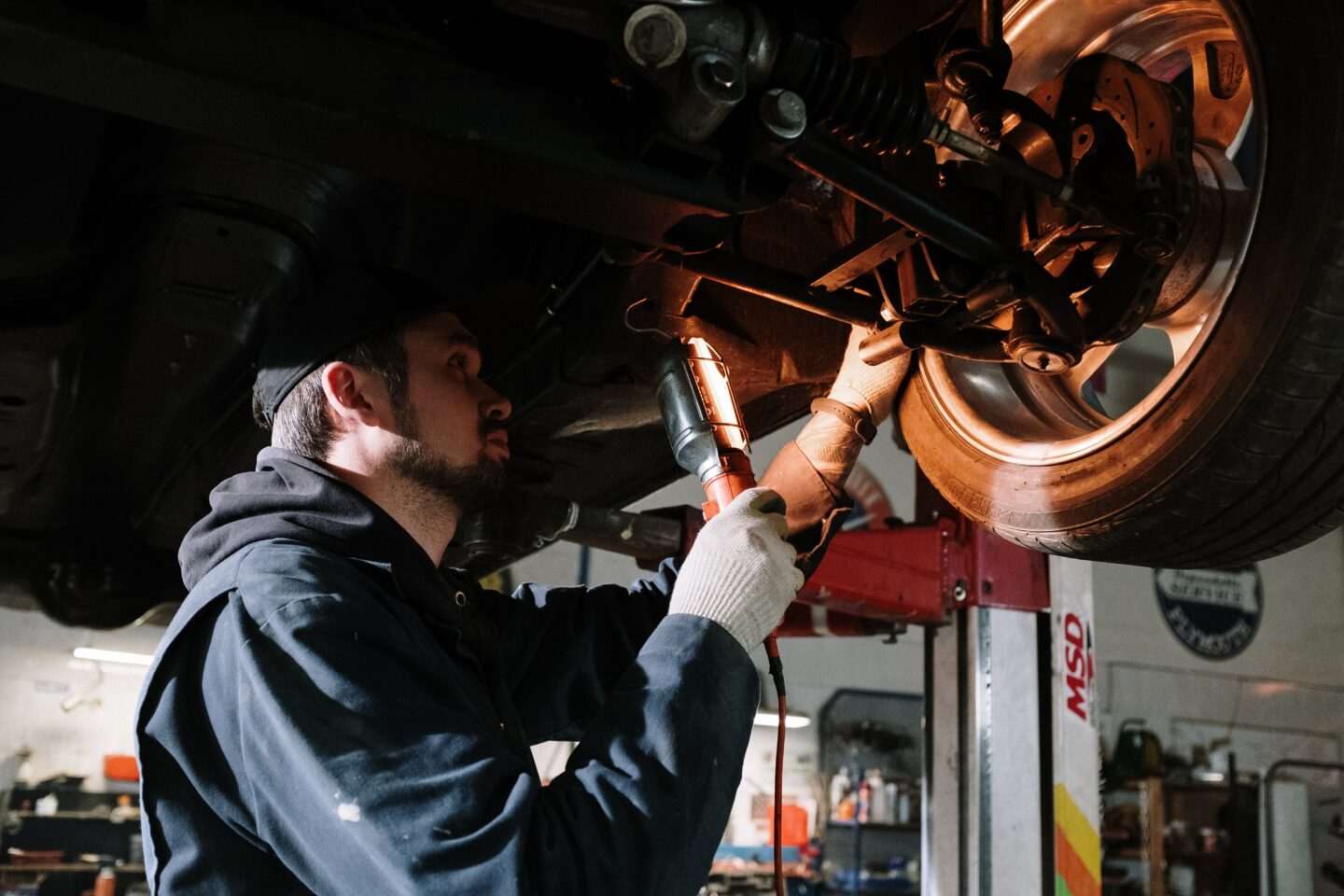 The auto mechanic is inspecting suspension of a car
