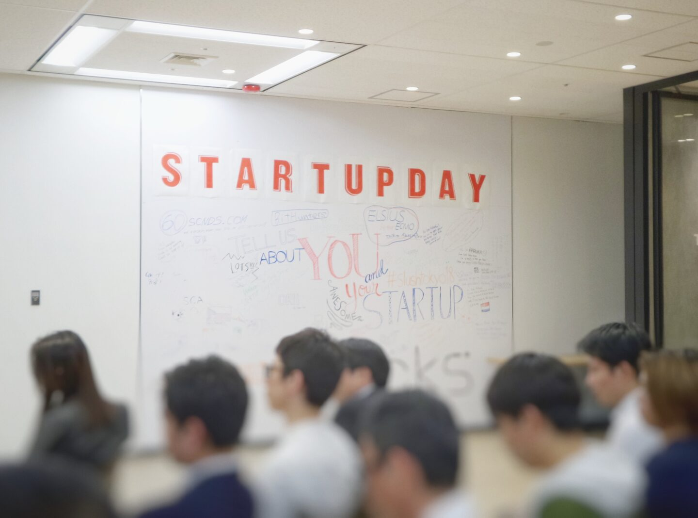 The group of people is learning in the office with a whiteboard on the wall with caption Startupday