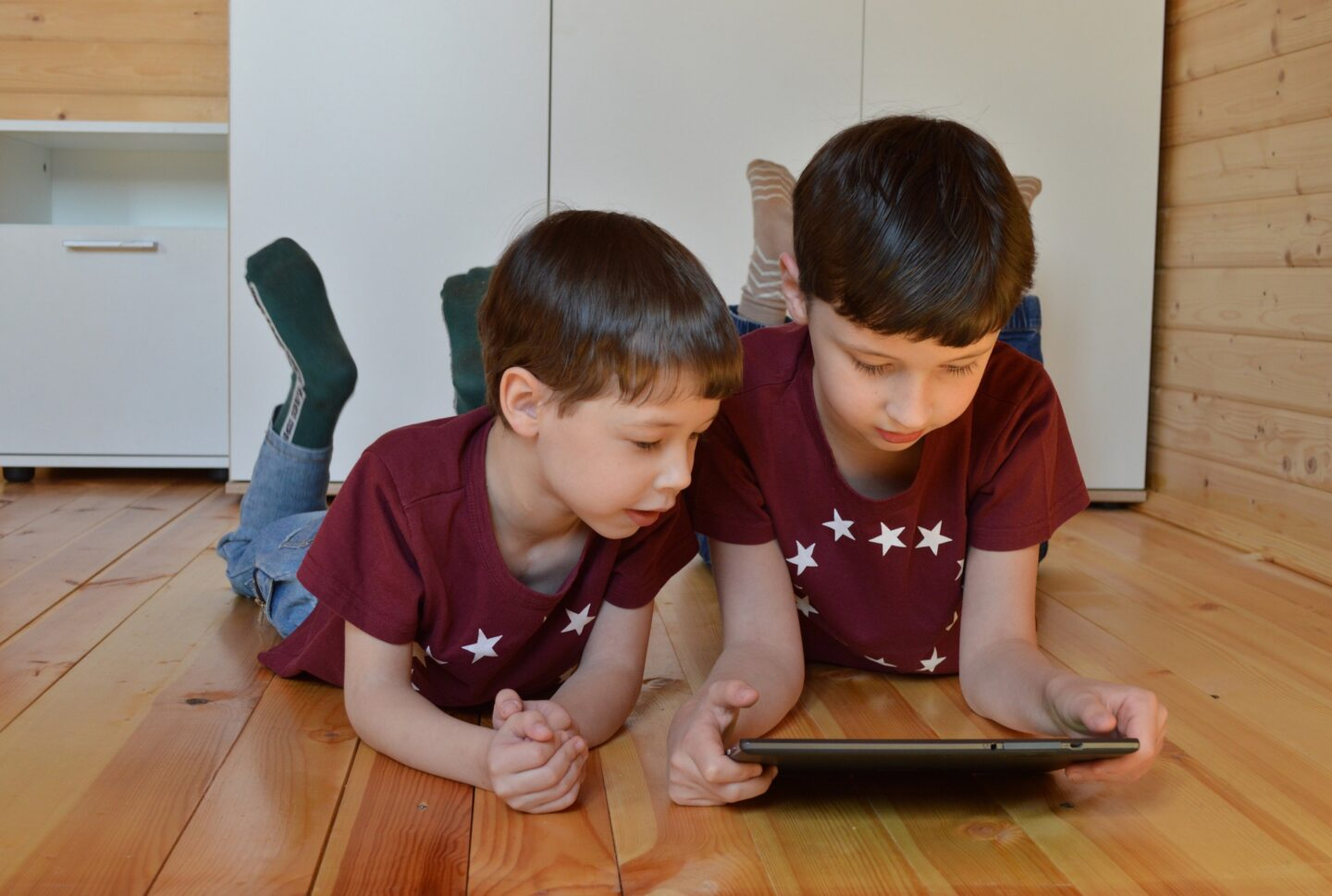 Two kids are lying on the floor and watching a tablet PC