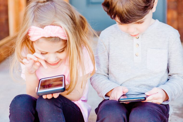 Little girl and boy sit with smartphones, they are happy to see something interesting