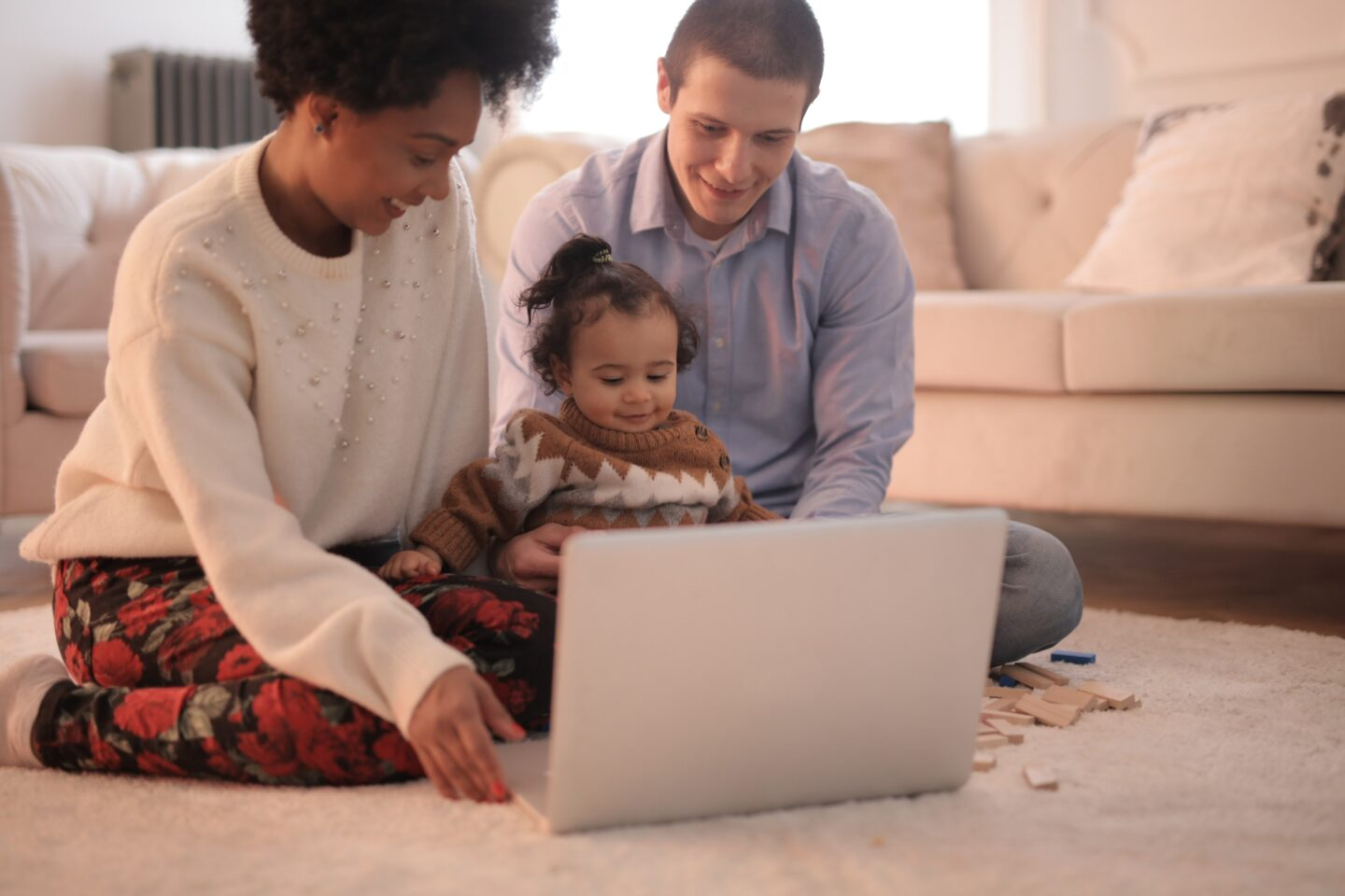 Parents and the kid sit on the floor with a grey laptop in the light room