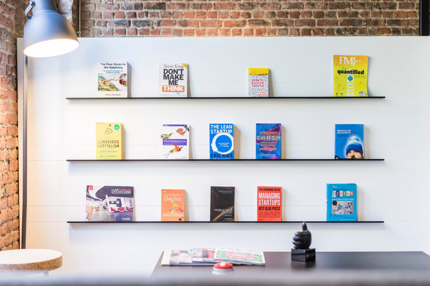 The bookshelf with books about web design. UX and UI in the office symbolyze the importance of knowledje to achieve the business success