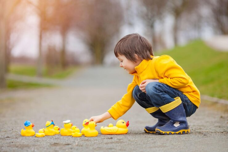 A boy is playing with rubber ducks on the street
