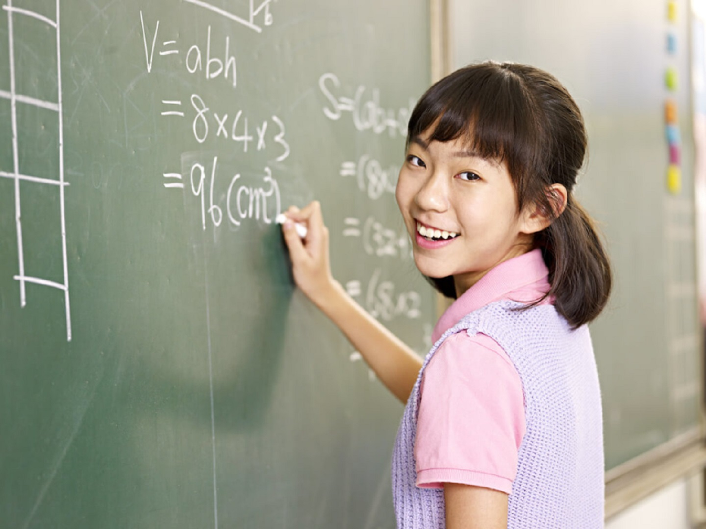 A girl is writing formulas on a blackboard