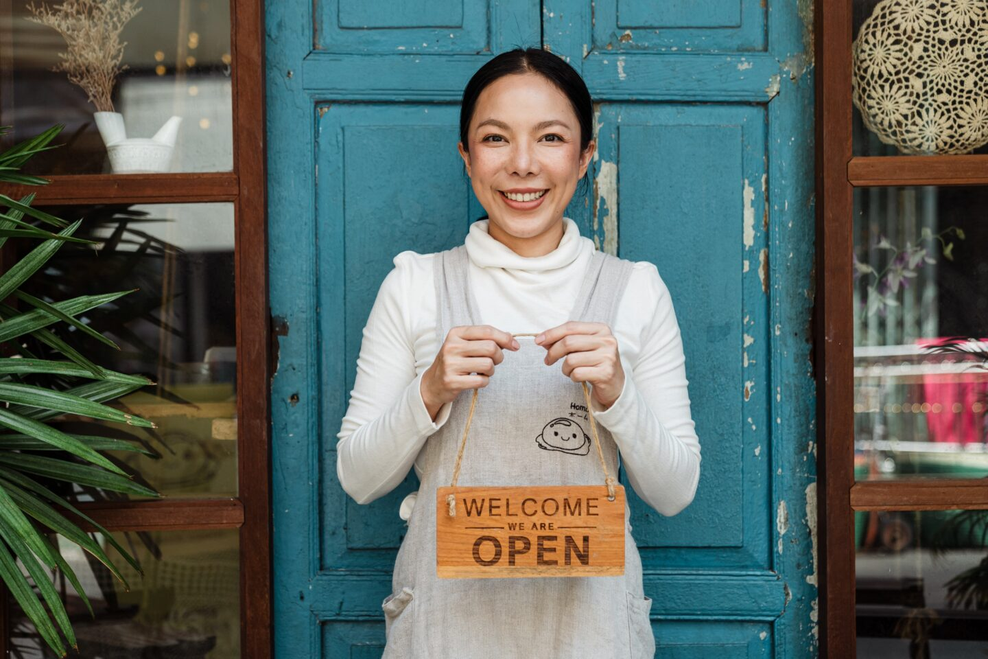 A woman is holding a sign Open, Welcome that means her business is opened.